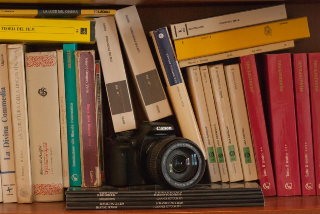 Una macchina fotografica è incastrata tra i libri di uno scaffale a simboleggiare il mix tra cultura e tecnica in un servizio fotografico