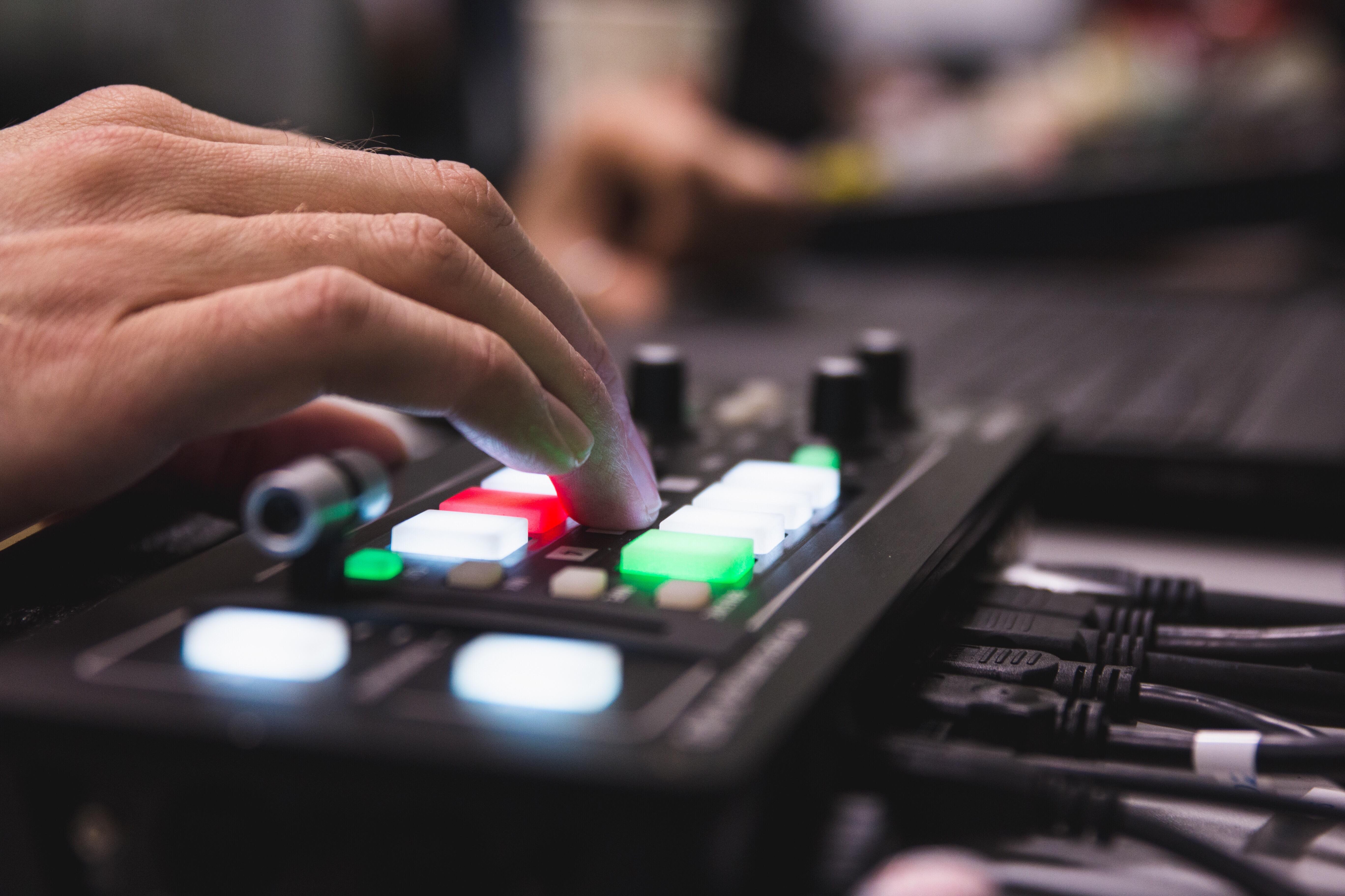 Una mano opera su di un mixer video per riprese video in diretta streaming live sul web.